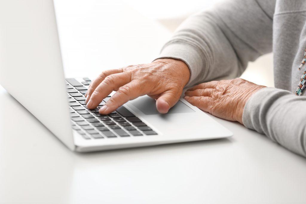 An elderly man at a laptop