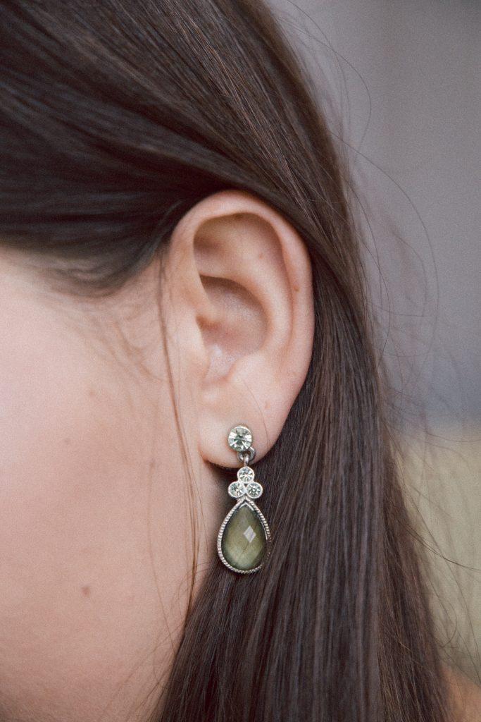 A woman wearing a tear drop earring
